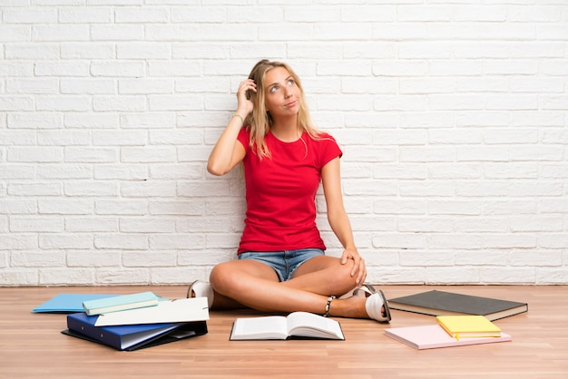 Jeune étudiante blonde avec beaucoup de livres sur le sol ayant des doutes et avec une expression de visage confuse Photo Premium