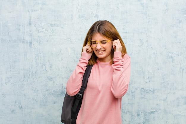 Jeune étudiante en colère, stressée et agacée, couvrant les deux oreilles d'un bruit assourdissant, du son ou de la musique forte Photo Premium