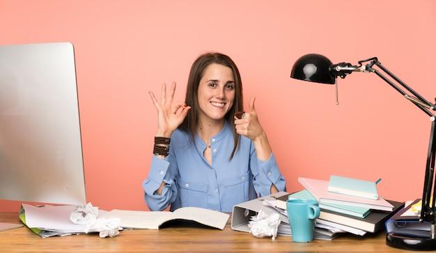 Jeune étudiante fille montrant ok signe et pouce en haut geste Photo Premium
