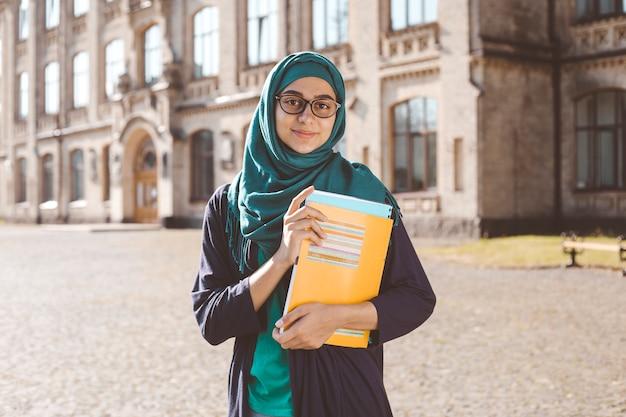Jeune étudiante musulmane souriante tenant des livres debout près du collège. heureuse jeune fille arabe en hijab. femme asiatique sur la formation. Photo Premium