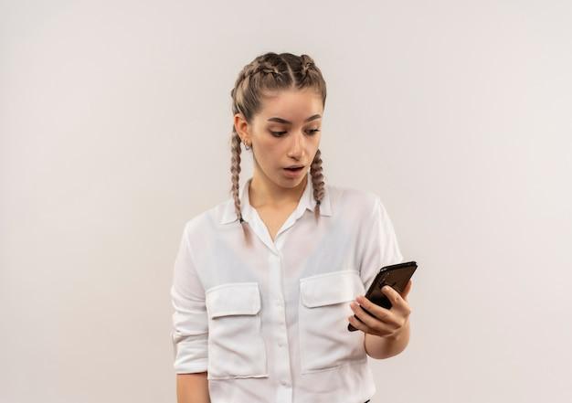 Jeune étudiante Avec Des Nattes En Chemise Blanche à La Recherche De L'écran De Son Mobile Avec Une Expression De Confusion Debout Sur Un Mur Blanc Photo gratuit