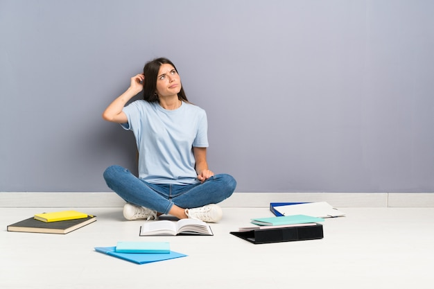 Jeune étudiante avec de nombreux livres au sol ayant des doutes et avec une expression de visage confuse Photo Premium