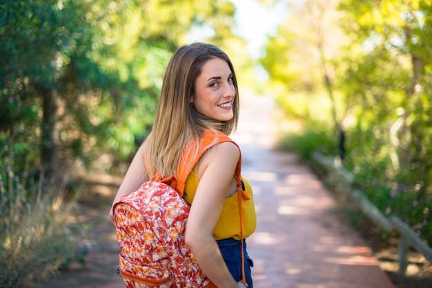 Jeune étudiante avec sac à dos dans un parc Photo Premium
