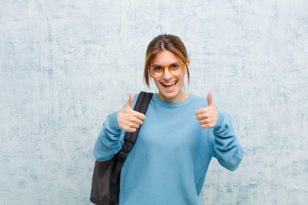 Jeune étudiante souriante, souriante, heureuse, positive, confiante et performante, les deux pouces contre grunge Photo Premium