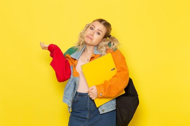 Jeune étudiante En Vêtements Modernes Tenant Des Fichiers Jaunes Posant Sur Jaune Photo gratuit