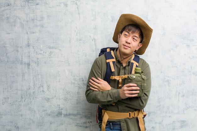 Jeune Explorateur Chinois Souriant Aux Bras Croisés, Levant Les Yeux Photo Premium