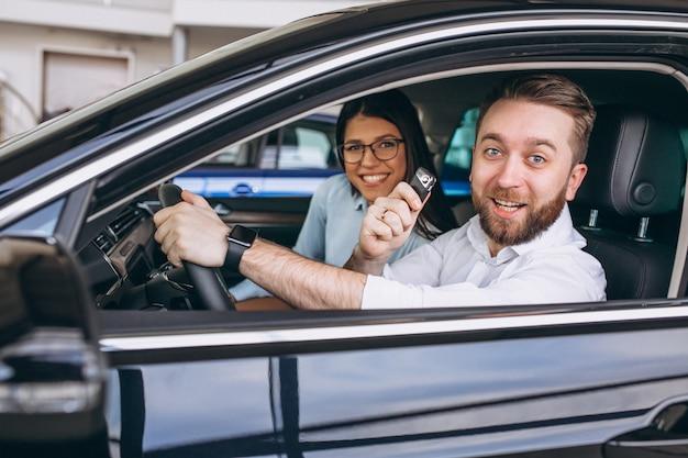 Jeune famille achète une voiture Photo gratuit