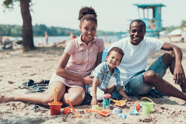 Une jeune famille afro-américaine est assise sur la plage de sandy river. Photo Premium