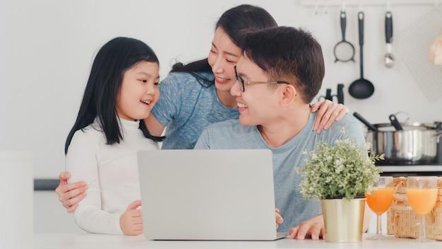 Jeune famille asiatique aime utiliser un ordinateur portable ensemble à la maison. mode de vie jeune mari, femme et fille heureux câlin et jeu après le petit déjeuner dans la cuisine moderne à la maison le matin. Photo gratuit