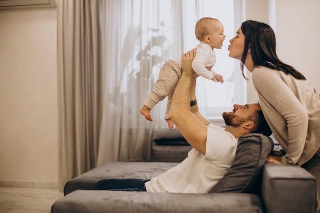 Jeune Famille Avec Bébé Fille Assise Sur L'entraîneur à La Maison Photo gratuit