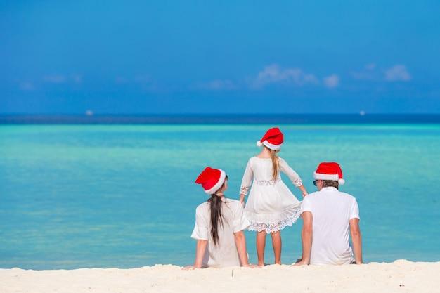 Jeune famille en chapeaux santa pendant les vacances de noël Photo Premium