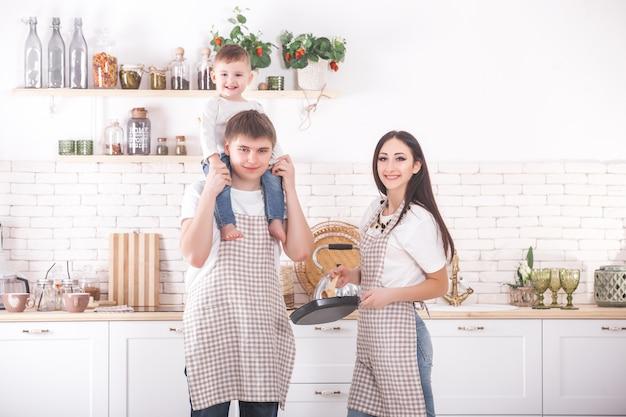 Jeune Famille Cuisiner Ensemble. Mari, Femme Et Leur Petit Bébé Dans La Cuisine. Famille Pétrir La Pâte Avec De La Farine. Les Gens Préparent Le Dîner Ou Le Petit Déjeuner. Photo Premium
