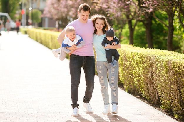 Jeune famille avec deux enfants en promenade Photo Premium