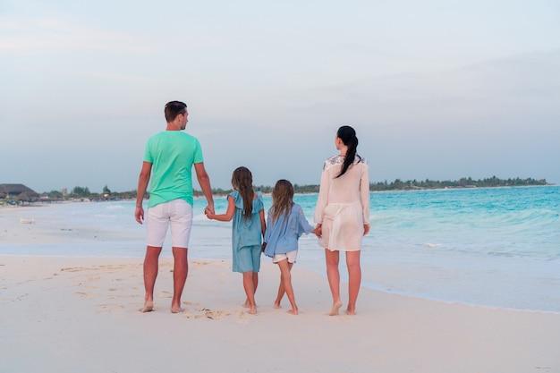 Jeune famille avec deux enfants en vacances à la plage Photo Premium