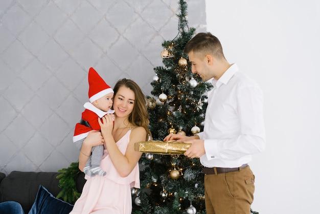 Une Jeune Famille Fête Noël à La Maison Dans Le Salon Près De L'arbre De Noël. Heureuse Maman, Papa Et Fils Profitent De Leurs Vacances Ensemble. Le Père Donne Un Cadeau à La Mère Et Au Bébé Photo Premium