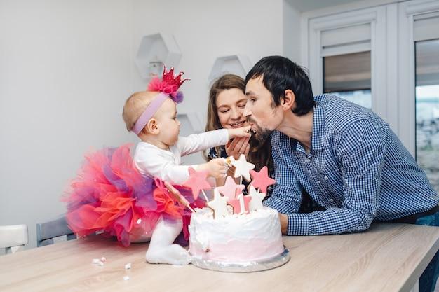 Jeune famille fête son anniversaire avec un gâteau Photo Premium