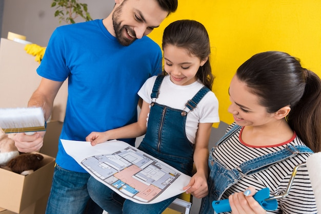 Jeune famille heureuse étudie la disposition des pièces dans la maison. Photo Premium