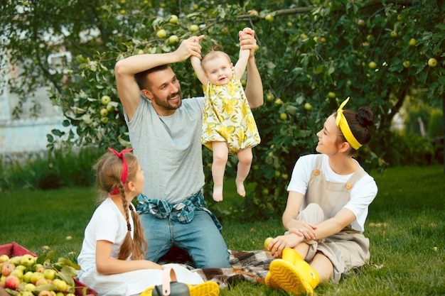 La Jeune Famille Heureuse Lors De La Cueillette Des Pommes Dans Un Jardin En Plein Air Photo gratuit