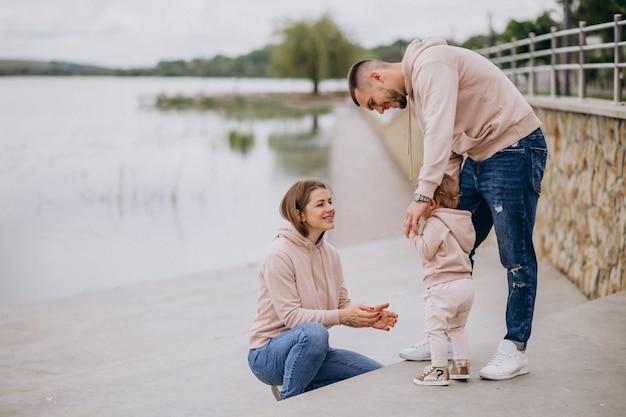 Jeune famille avec leur petit bébé dans un parc au bord du lac Photo gratuit