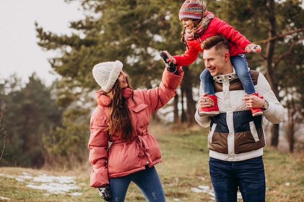 Jeune Famille Marchant Ensemble Dans La Forêt à L'heure D'hiver Photo gratuit
