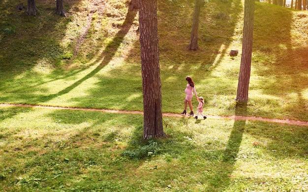 Jeune famille une mère enceinte et sa fille aînée se promènent dans un parc urbain en été par temps ensoleillé Photo Premium