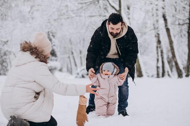 Jeune Famille Avec Petite Fille Dans Une Forêt D'hiver Pleine De Neige Photo gratuit