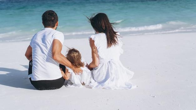 Jeune famille avec petite fille en vacances au bord de l'océan Photo gratuit