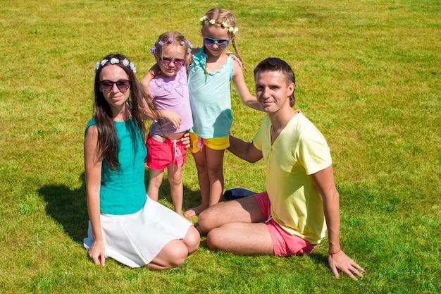 Jeune famille de quatre personnes assises sur l'herbe et s'amuser Photo Premium