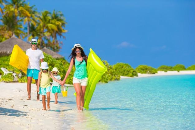 Jeune famille de quatre en vacances à la plage Photo Premium
