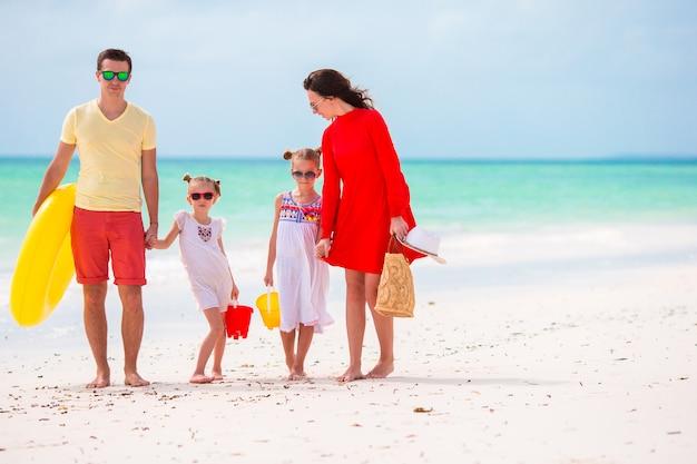 Jeune famille en vacances. heureux père, mère et leurs enfants mignons s'amusant pendant leurs vacances d'été à la plage Photo Premium