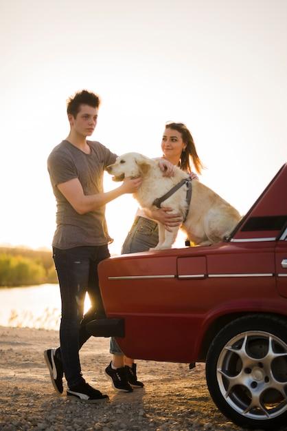 Jeune famille en voyage avec leur chien Photo gratuit