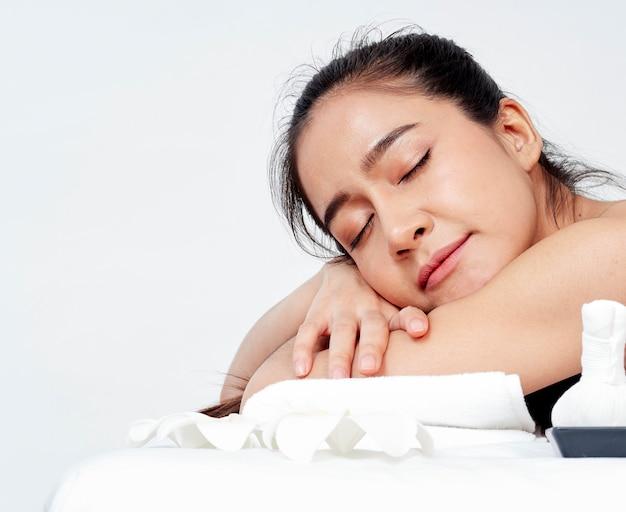 Jeune femme et accessoires de spa sur table de massage Photo Premium