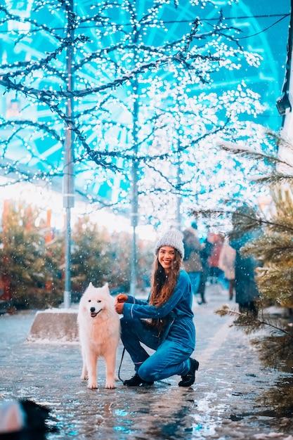 Jeune Femme Accroupie à Côté D'un Chien Dans Une Rue D'hiver Photo gratuit