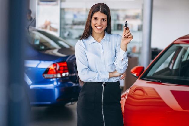 Jeune femme achète une voiture Photo gratuit