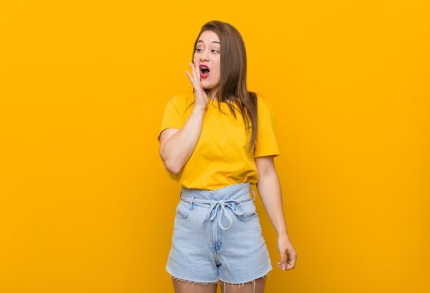 Jeune Femme Adolescente Portant Une Chemise Jaune Dit Une Nouvelle Secrète De Freinage à Chaud Et à Côté Photo Premium