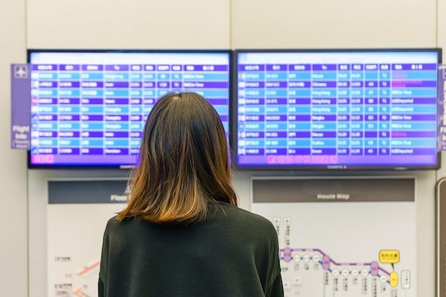 Jeune femme à l'aéroport international en regardant le panneau d'information de vol Photo Premium