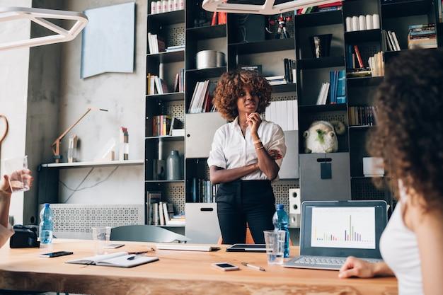 Jeune femme d'affaires africaine debout dans le bureau de co-working et travaillant sur le projet Photo Premium
