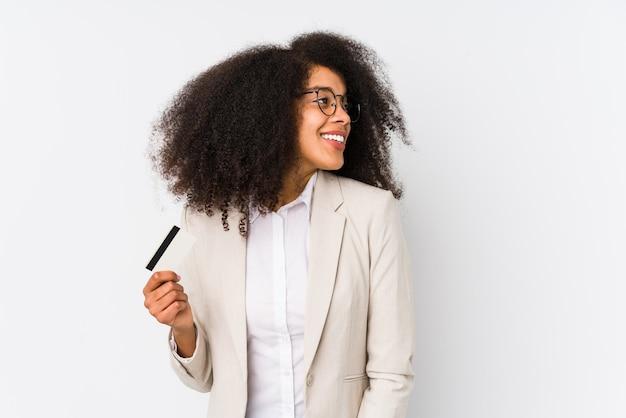 Jeune Femme D'affaires Afro Tenant Une Voiture De Crédit Isolée Jeune Femme D'affaires Afro Tenant Une Voiture De Crédit Semble De Côté Souriant, Joyeux Et Agréable. Photo Premium