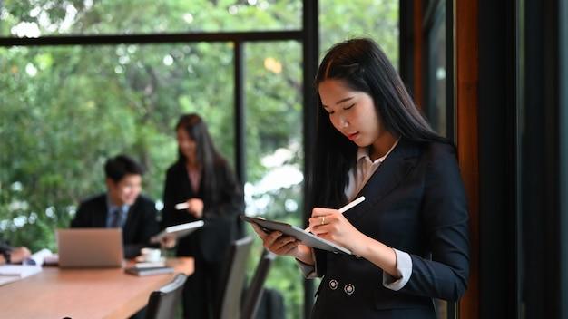 Jeune Femme D'affaires à L'aide De Stylet Rabotage écrit Son Projet Sur Tablette Dans La Salle De Réunion. Photo Premium