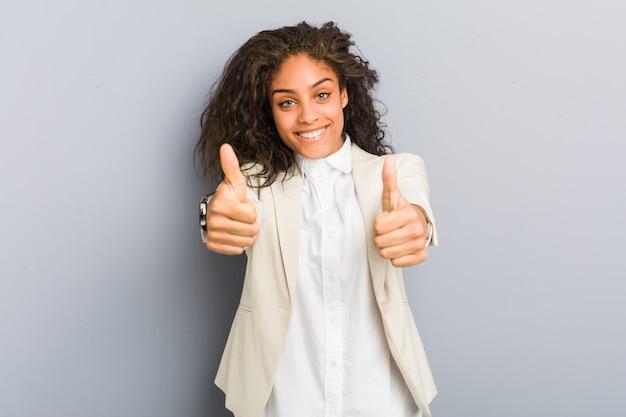 Jeune femme d'affaires américaine africaine avec le pouce levé, acclamations à propos de quelque chose, de soutien et de respect concept. Photo Premium