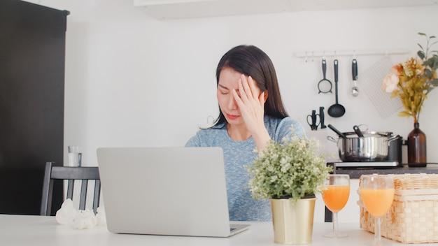 Jeune femme d'affaires asiatique enregistre les revenus et les dépenses à la maison. dame inquiète, sérieuse, stressée lors de l'utilisation d'un budget record sur ordinateur portable, de la taxe, d'un document financier travaillant dans la cuisine moderne de la maison. Photo gratuit