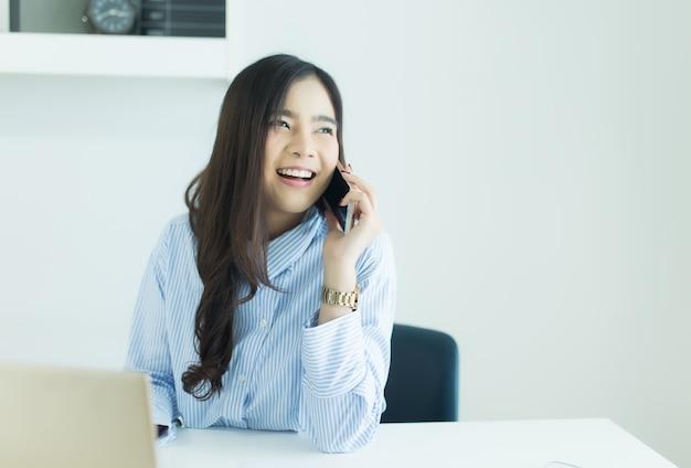 Jeune femme d'affaires asiatique parlant au téléphone mobile et souriant sur son lieu de travail Photo Premium