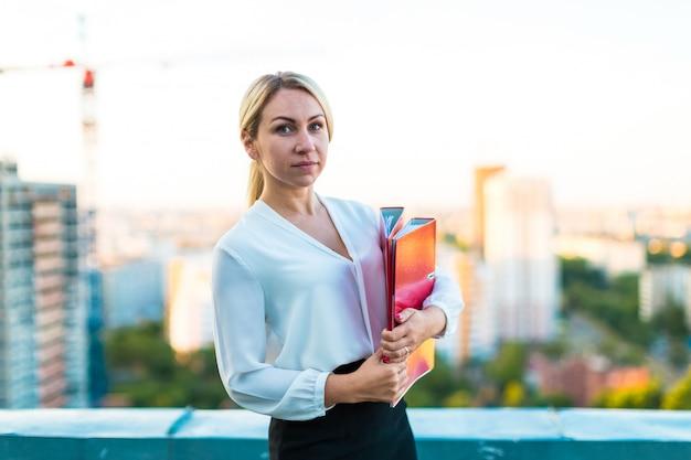 Jeune femme d'affaires attrayante debout sur le toit avec une chemise en papier dans les mains Photo Premium