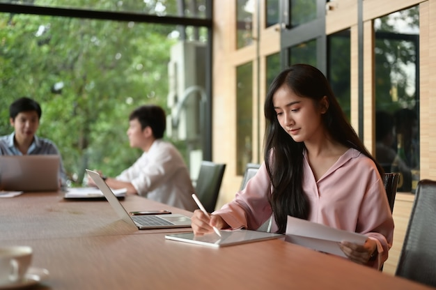 Jeune Femme D'affaires Au Bureau De Démarrage Moderne Travaillant Sur Tablette, équipe Estompée En Arrière-plan De Réunion. Photo Premium