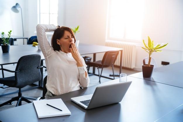 Jeune, femme affaires, bâiller, à, a, bureau moderne, devant, ordinateur portable Photo Premium