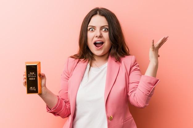 Jeune femme d'affaires bien roulée taille tenant un lingot d'or célébrant une victoire ou un succès Photo Premium