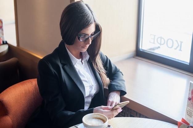 Jeune femme d'affaires, boire du café au café et lire un mail téléphonique Photo Premium