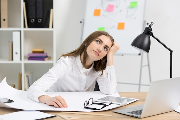 Jeune femme d'affaires contemplée avec du papier blanc; lunettes et tablette numérique sur le bureau en bois Photo gratuit