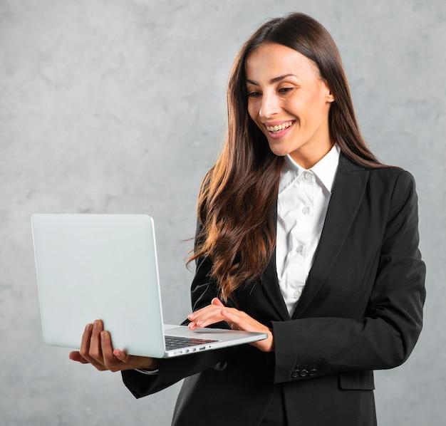 Jeune, femme affaires, dactylographie, debout, ordinateur portable, contre, fond gris Photo gratuit