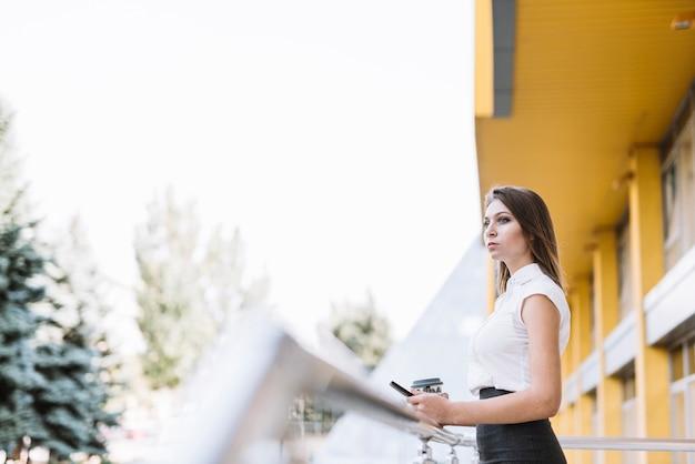 Jeune, femme affaires, debout, balcon, tenue, téléphone portable, et, tasse à café Photo gratuit
